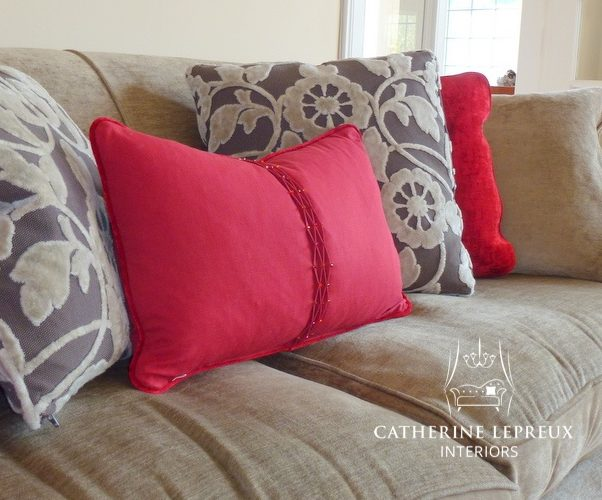 Bespoke red scatter cushions add impact to a neutral velvet sofa